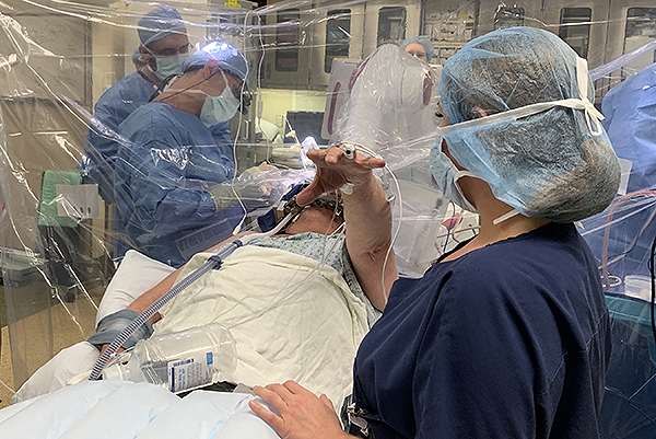 A patient's tremor is tested in the operating room during DBS surgery.
